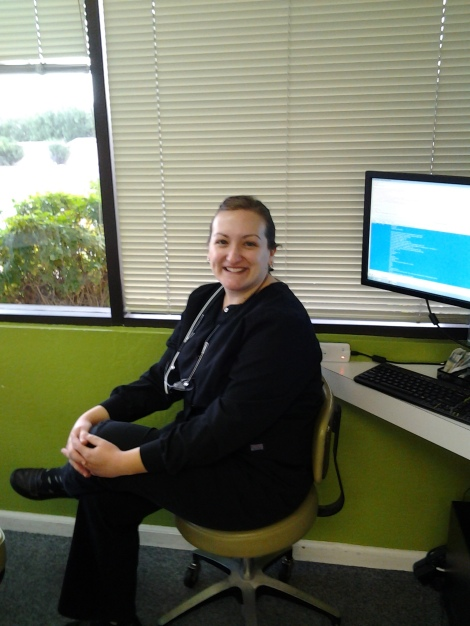 A White woman (Registered Dental Hygienist) is sitting her office with smile.