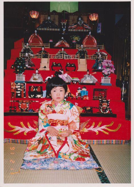 ひな壇飾りと着物を着た少女がその前で座り微笑む画像